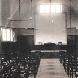 The North End of the Main Hall C 1930 - Permanent Stage with Screen at Back . Wooden Chairs Which were used until the 1970's